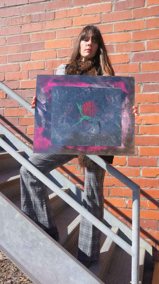 Artist Rachael Harbert holds painting Rose as she stands on a metal staircase and closes her eyes as the sunlight shines brightly on her