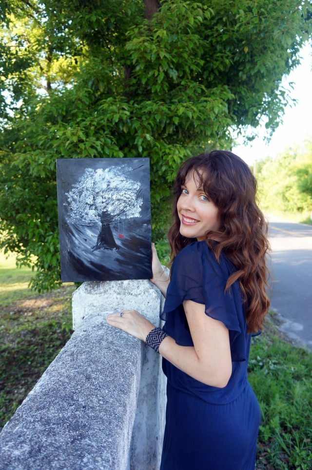 "Artist Rachael Harbert stands next to painting ""White Tree"" as it sits on side of rustic white cement bridge"