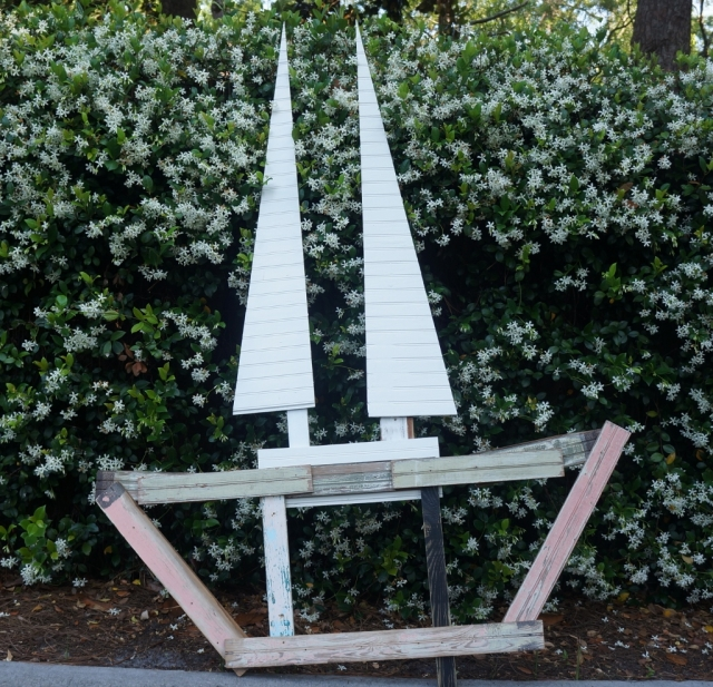 Large sailboat sculpture made from repurposed 1920s wood against green vine background