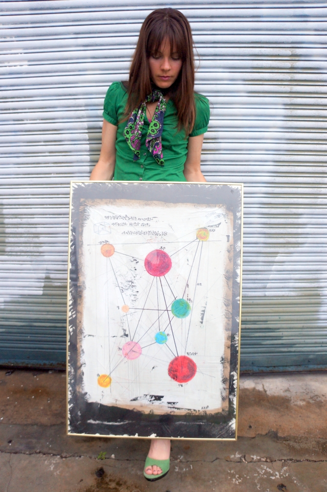 "Artist Rachael Harbert holds painting ""The Map"""