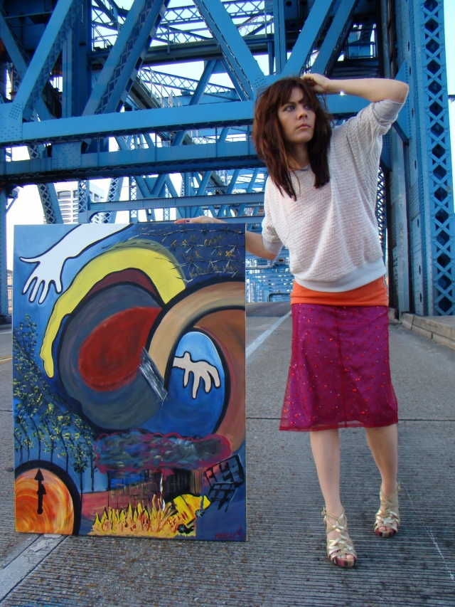"Artist Rachael Harbert propping up pop art painting ""Pop Mission"" as she stands in the middle of a large blue metal bridge"