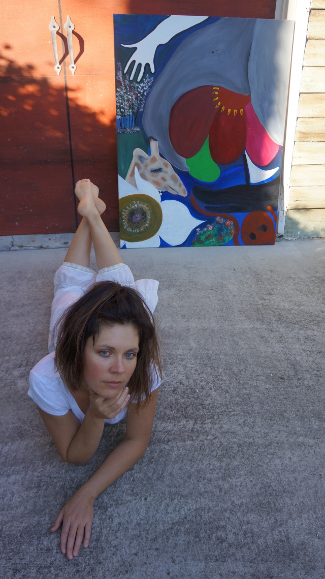 """Artist Rachael Harbert laying on the ground in front of pop art painting """"Pop Mission"""" as it leans against a red garage door"""
