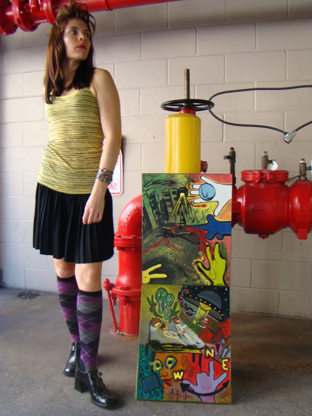 Artist Rachael Harbert with paintings Shadowplay and Extraterrestrial leaning against large red and yellow pipes