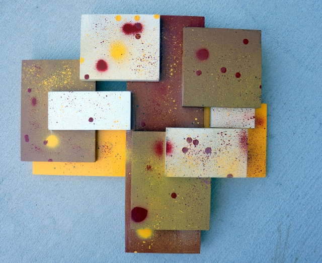 Sculpture made from wood assembled and painted red, gold and white with droplets of paint splattered on top of each block